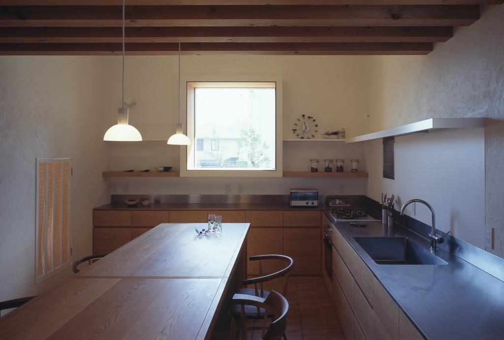 三重県で建築家による注文住宅づくり。白い漆喰の壁に正方形の窓の壁付けキッチンです