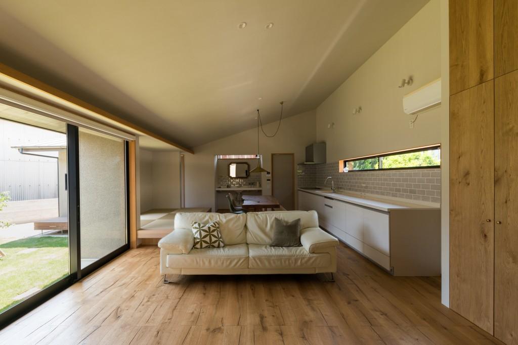 三重県津市 建築家の家 自然素材のリビング 勾配天井 無垢の床板 大きなキッチン