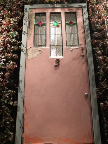 ステンドグラスが入ったピンクの玄関ドア