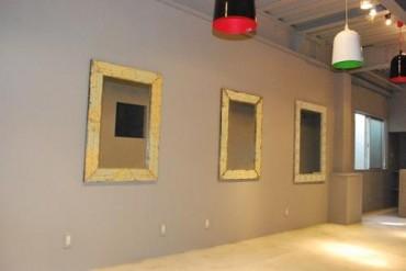 グレーの壁に映えるアンティークな額縁の鏡